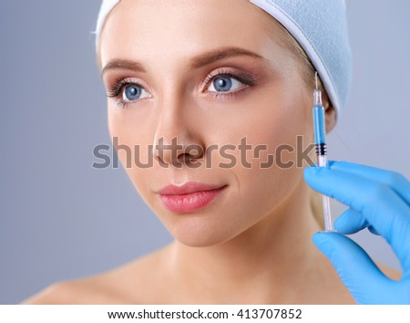 Cosmetic injection on the pretty woman face. Isolated on gray background - stock photo