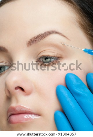 Cosmetic injection to the pretty female face. Injecting to the eye. - stock photo