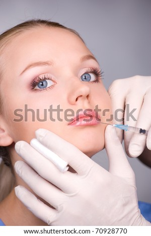 cosmetic injection to the pretty female lips - close-up portrait