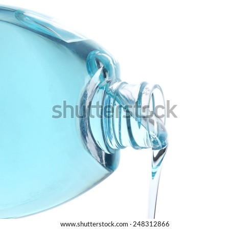 Cosmetic liquid pouring from bottle isolated on white - stock photo