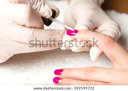Cosmetic manicured fingernails with fuchsia nail polish on a soft white towel.