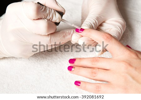 Cosmetic manicured fingernails with fuchsia nail polish on the soft white towel.
