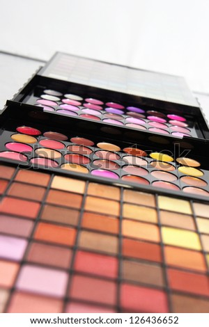 Cosmetic palette over white background with a lot of vivid bright colors - stock photo