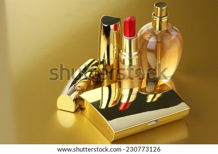 Cosmetic set. Gold powder, lipsticks and perfume on golden background. - stock photo