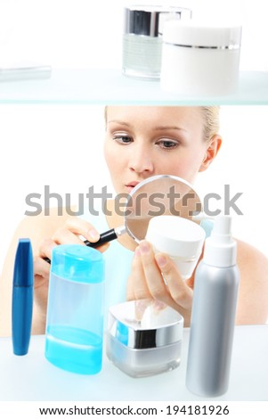 Cosmetic shopping - woman reading label. A woman stands at the client shelf and looks at the composition of creams  - stock photo