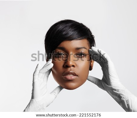cosmetic surgery concept. Doctor's hand holding a face - stock photo