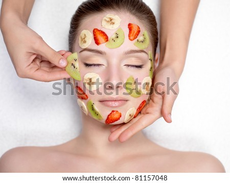 Cosmetician doing fruit mask on a face of beautiful young woman - indoors - stock photo