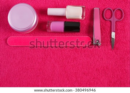 Cosmetics and accessories for manicure or pedicure on fluffy towel, nail file, nail polish and remover, scissors, nail clippers, concept of nail care, copy space for text - stock photo