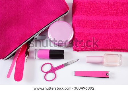 Cosmetics and accessories for manicure or pedicure, pink bag cosmetic, nail file, nail polish and remover, scissors, nail clippers, fluffy towel, concept of nail care - stock photo