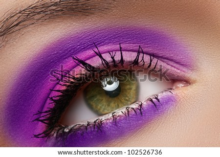 Cosmetics and beauty care. Macro close-up of beautiful green female eye with bright fashion runway make-up. Violet eyeshadows and black eyeliner