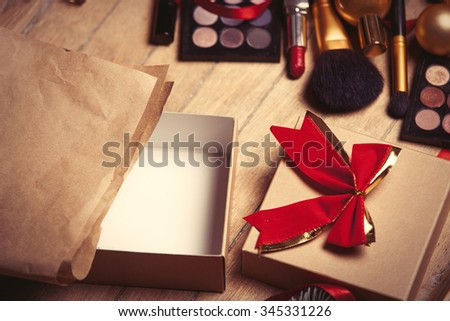 cosmetics and christmas gifts on wooden background