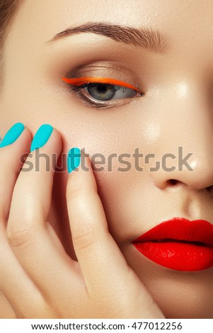 Cosmetics and makeup. Woman's face with vivid make up and colorful nail polish. Colourful nails. Closeup portrait of fashion model with red lips and mint manicure. Smoky eyes and long eyelashes