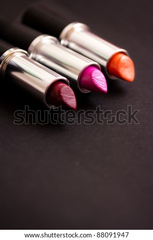 cosmetics: colorful lipsticks on black background