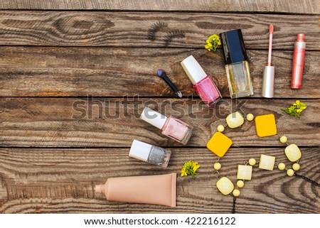 Cosmetics:, false eyelashes, concealer, nail polish, perfume, lip gloss, beads, and yellow flowers on wooden background. Toned image.  - stock photo