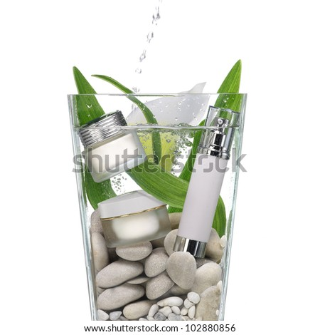 Cosmetics in a vase of water with stones and green leaves - stock photo