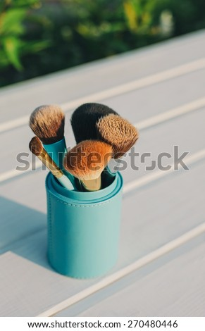 Cosmetics. Makeup brushes of different color and size on white wooden background against green grass outdoor - stock photo