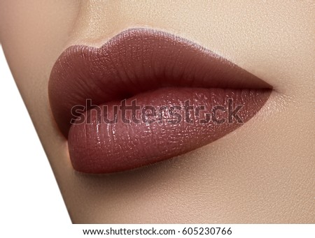 Cosmetics, makeup. Dark fashion lipstick on lips. Closeup beautiful female mouth with sexy lip makeup. Part of face. Plump lips