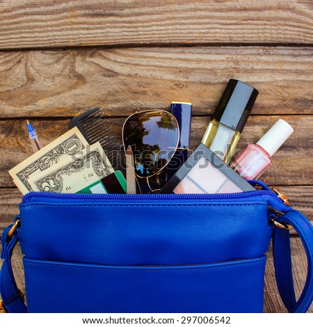 Cosmetics, money and women's accessories fell out of blue handbag on wood background.