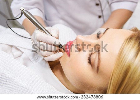 Cosmetologist applying permanent make-up on lips - stock photo