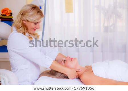 cosmetologist doing facial massage beautiful girl. Beauty