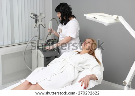 Cosmetologist tuning of the laser for hair removal. The patient lies flat on the couch. - stock photo
