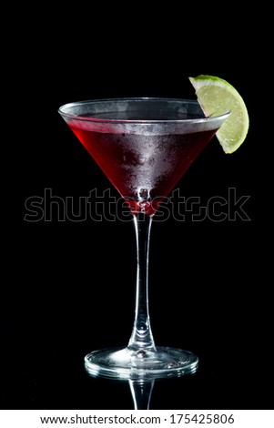 cosmopolitan martini served with a lime isolated on a black background