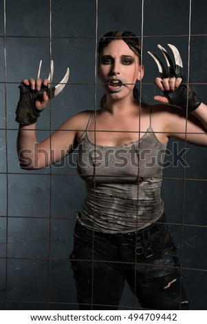 Cosplay warrior behind a wire mesh fence