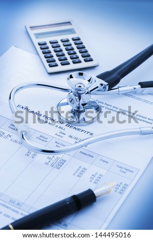 Cost of health care with stethoscope, calculator and pen - stock photo