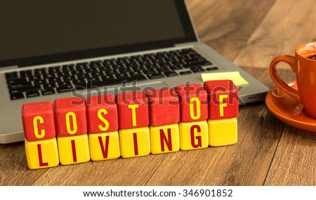 Cost of Living written on a wooden cube in a office desk - stock photo