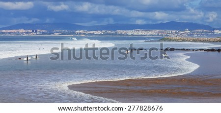 Costa de Caparica, Portugal. April 19, 2015: Surfers in the beach with Lisbon in background. This is an iconic location for surf in Portugal because its one of the pioneer beaches and quality of waves - stock photo