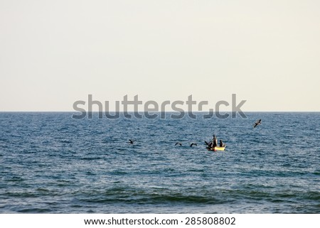 Costa del Sol, La Paz / El Salvador - February 4, 2014: A pair of traditional fishermen ride in a small vessel nearby the shore, fishing with a net while pelicans fly around.