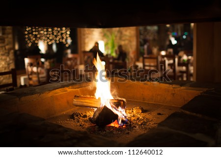 Cosy fireplace in a mountain chalet's warm, wooden interior - stock photo