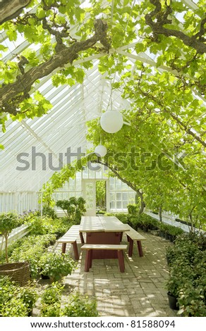Cosy green romantic conservatory greenhouse with table and benches. - stock photo