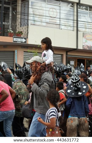 COTACACHI, ECUADOR - JUNE 25, 2016: Inti Raymi, the Quechua solstice celebration, with a history of violence in Cotacachi.  Man carries his young daughter on his shoulders, past the dancing.