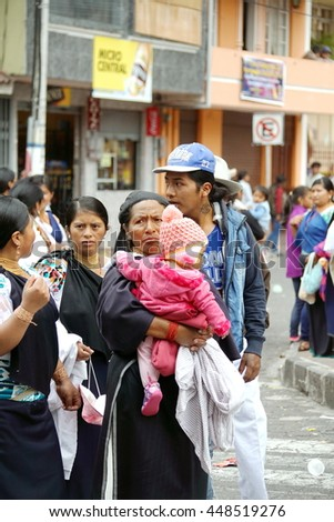 COTACACHI, ECUADOR - JUNE 30, 2016: Inti Raymi, the Quechua solstice celebration, with a history of violence in Cotacachi.  Women watching the parade, with one carrying an infant.