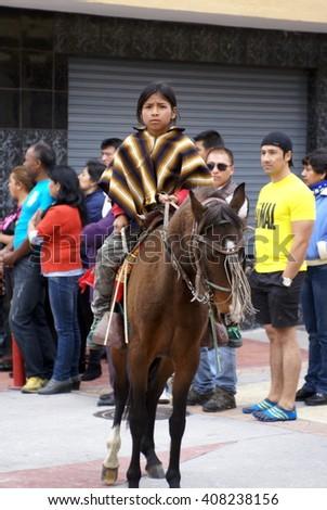 COTACACHI, ECUADOR - MAY 19, 2013: Girl in a poncho on a brown horse in the Paseo de Chagra, or horse parade - stock photo