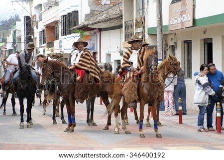 COTACACHI, ECUADOR - MAY 19, 2013: Paseo del Chagra (horse parade), horses in formation, riders in tan and brown ponchos - stock photo