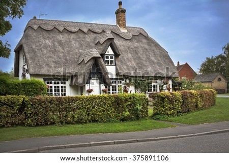 COTSWOLDS, UK - OCTOBER 12, 2014: Charming thatched roof house in the Cotswolds English countryside. - stock photo