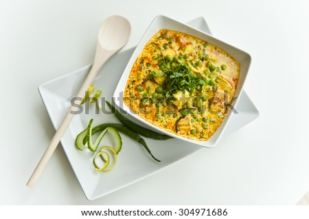 Cottage cheese and peas in a curry of curd - stock photo