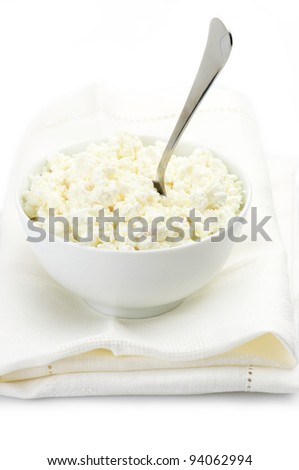 Cottage cheese and spoon in white bowl with linen napkin on white background. - stock photo