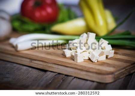Cottage cheese cubes with fresh vegetables on wooden table - stock photo
