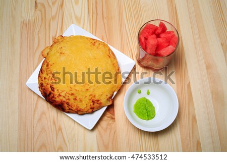 Cottage cheese flapjack flat cake and water-melon and wasabi on a wooden table