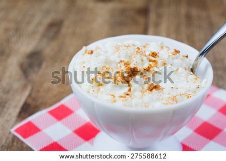 Cottage cheese garnished with paprika.  A spoon is dipped into the bowl.  Bowl is sitting on a red and white checkered napkin.
