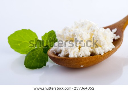 Cottage cheese in wooden spoon with basil leaves isolated on white background - stock photo