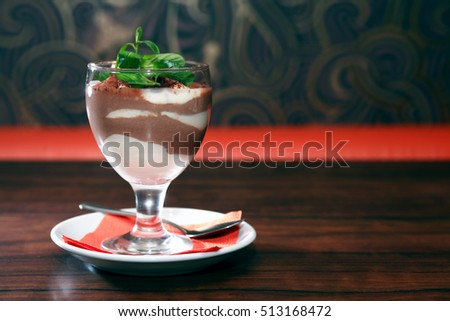 Cottage cheese mousse with chocolate in goblet on black table