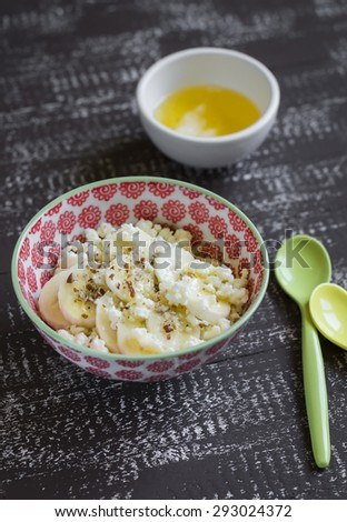 cottage cheese with banana, honey and pecan nuts in a bowl on a vintage dark wooden background - stock photo