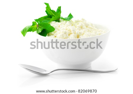Cottage cheese with mint in white bowl and spoon isolated on white background. - stock photo