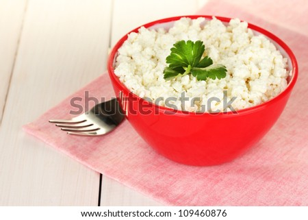 cottage cheese with parsley in red bowl and fork on pink napkin on white wooden table close-up - stock photo