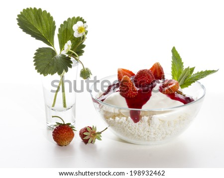 Cottage cheese with strawberries and yogurt in a transparent bowl on a white background