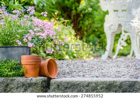 Cottage garden - beutiful flowers in pots with table and chair o - stock photo